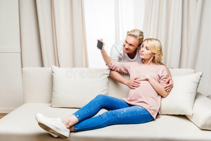Zwangere vrouw met echtgenoot het nemen selfie met smartphone thuis stock afbeelding
