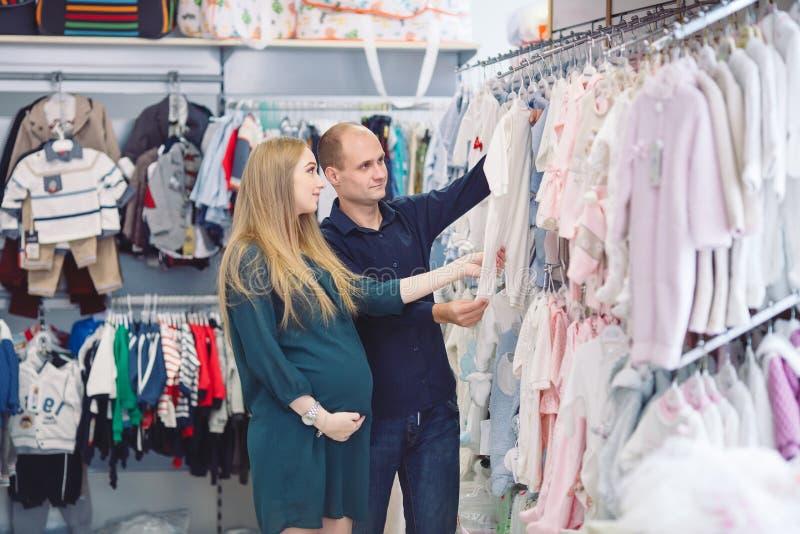 Zwangere vrouw met echtgenoot het winkelen voor baby stock foto's