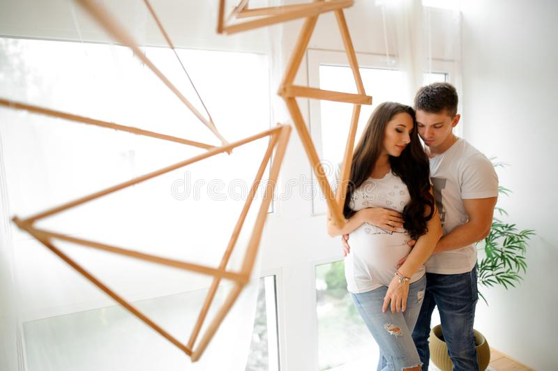 Zwangere vrouw met echtgenoot voor het venster royalty-vrije stock foto