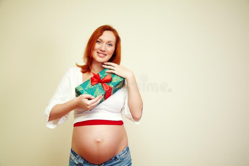 Zwangere vrouw met een gift royalty-vrije stock afbeelding