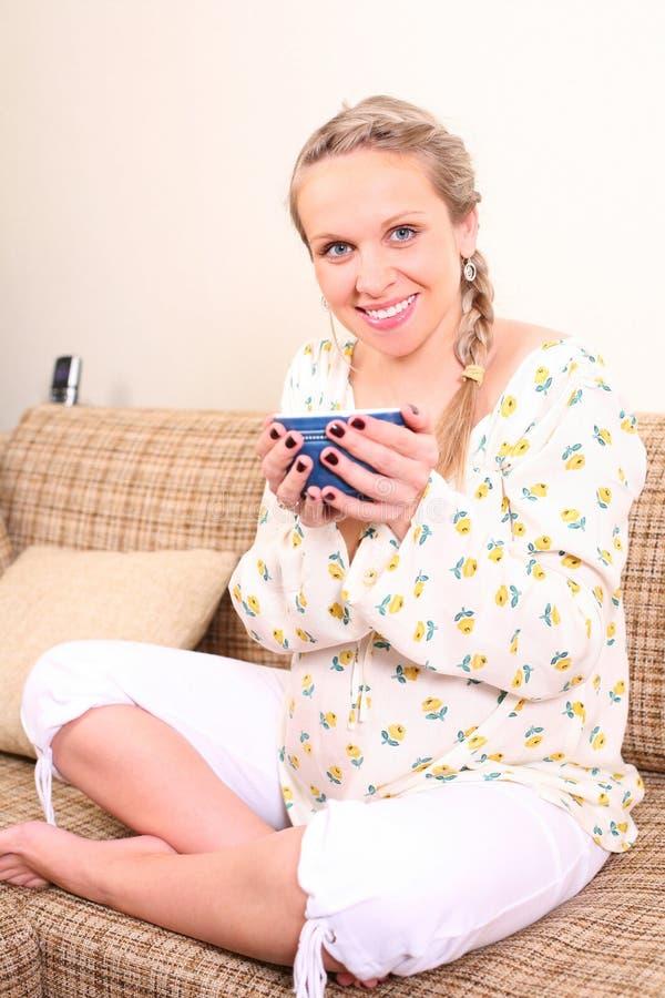 Zwangere vrouw met een kop thee stock fotografie