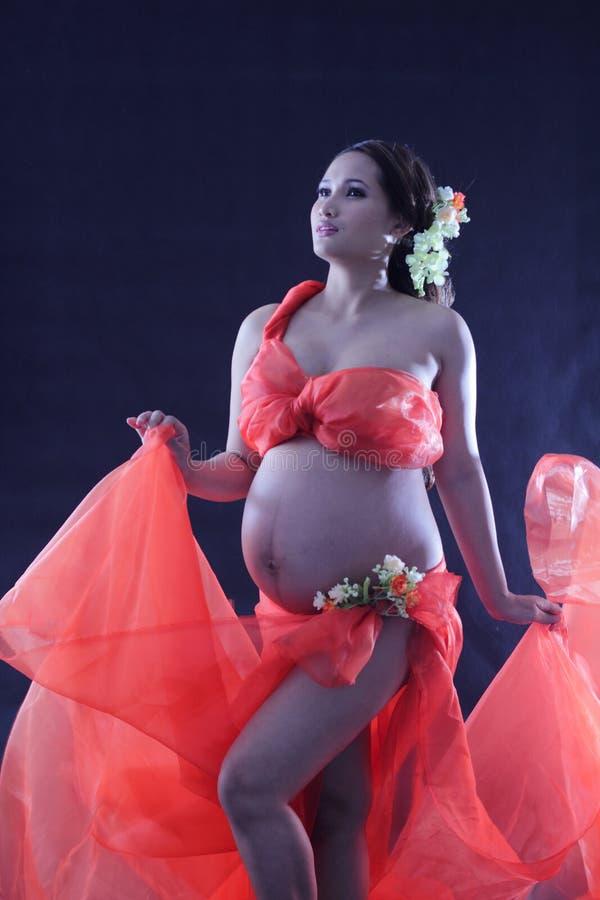 Zwangere vrouw met een rode kleding. stock foto