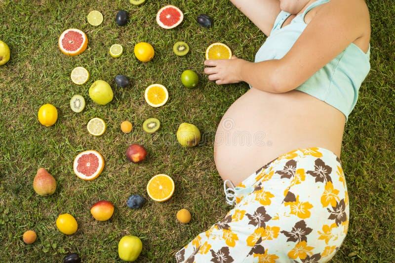 Zwangere vrouw met fruit stock fotografie