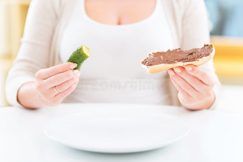 Zwangere vrouw met groenten in het zuur en chocoladesandwich stock fotografie