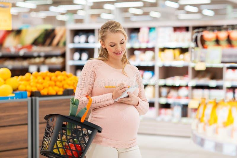 Zwangere vrouw met het winkelen mand bij kruidenierswinkel royalty-vrije stock afbeeldingen