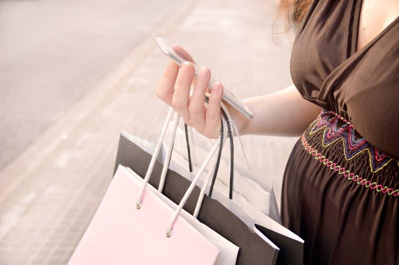 Zwangere vrouw met het winkelen zakken die slimme telefoon met behulp van stock afbeeldingen