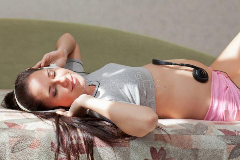 Zwangere vrouw met hoofdtelefoons royalty-vrije stock foto's