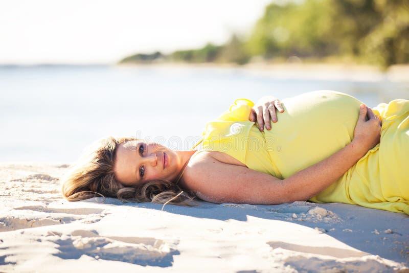 Zwangere vrouw met lang haar in gele kleding die op het strand liggen royalty-vrije stock afbeeldingen
