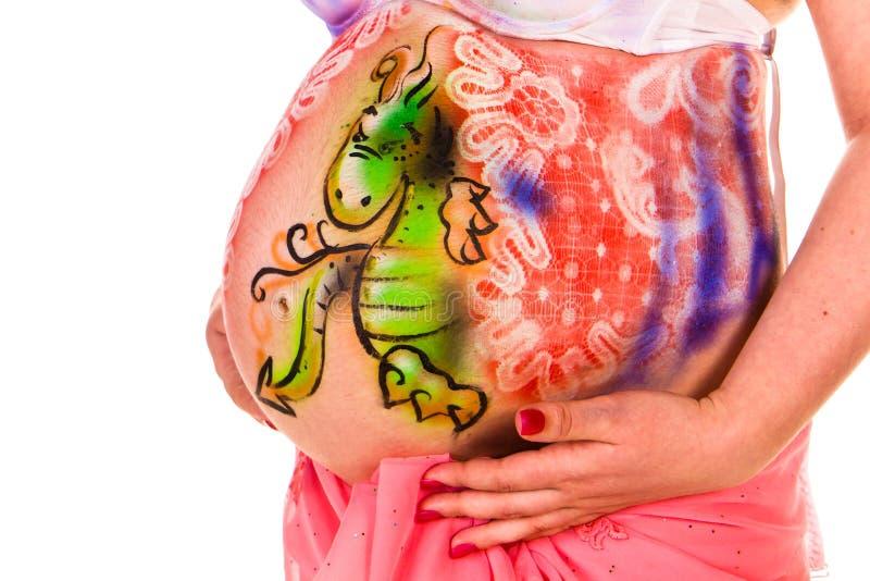 Zwangere vrouw met lichaam-kunst met littlledraak royalty-vrije stock afbeelding