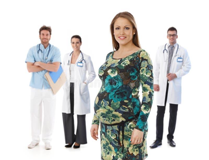 Zwangere vrouw met medisch team op achtergrond stock afbeeldingen