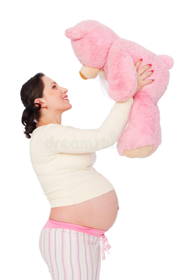 Zwangere vrouw met roze teddybeer stock afbeelding
