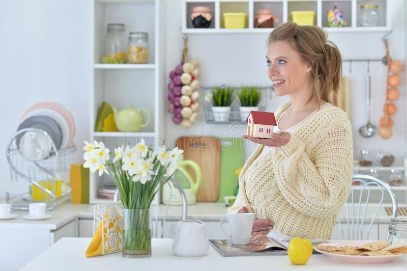 Zwangere vrouw met thee en tijdschrift royalty-vrije stock foto's
