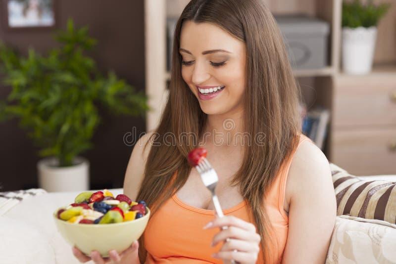 Zwangere vrouw met verse vruchten stock afbeeldingen