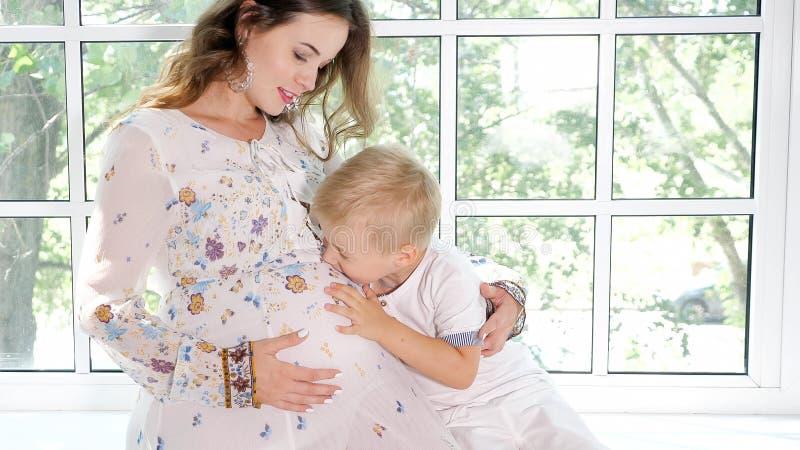 Zwangere vrouw met weinig zoon op venstervensterbank stock afbeelding