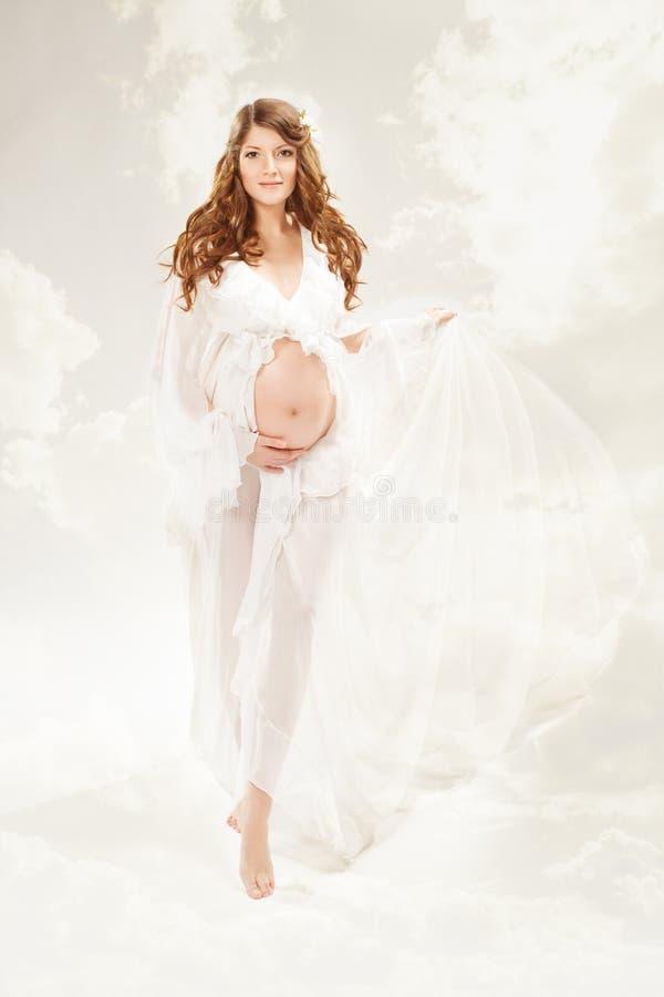 Zwangere vrouw. Mooie zwangerschap: lange krullende haar en chiffon stock foto's