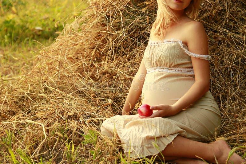 Zwangere vrouw op aard dichtbij de hooibergen royalty-vrije stock foto