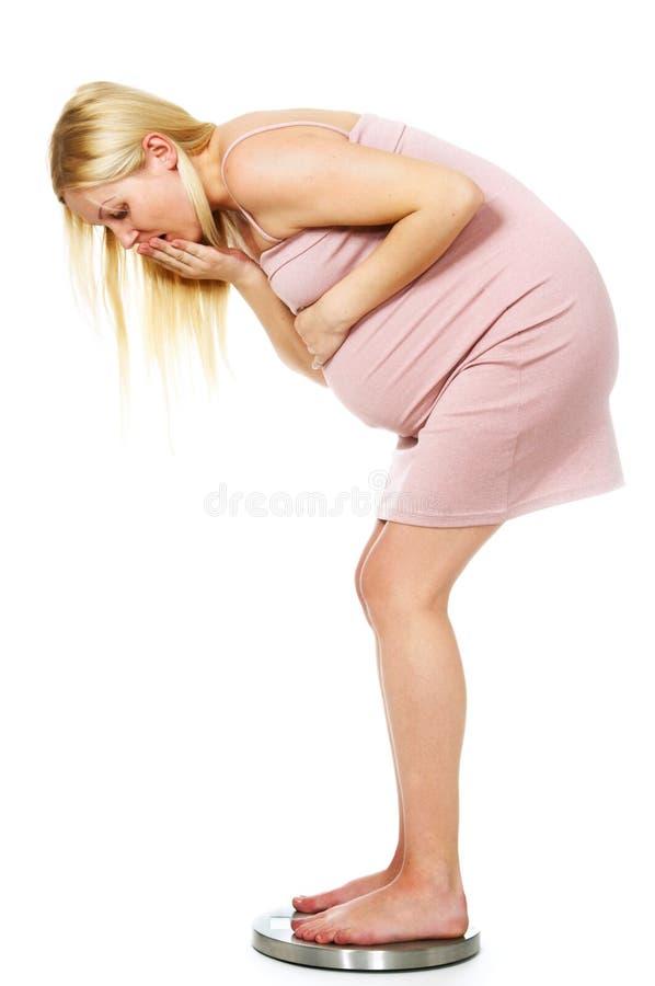 Zwangere vrouw op de schalen royalty-vrije stock fotografie
