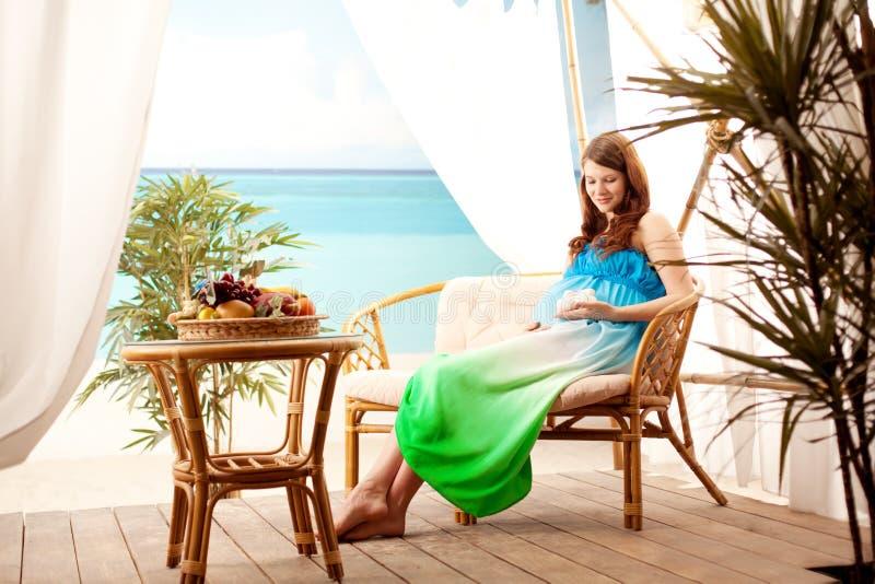 Zwangere vrouw op het strand in bungalow stock afbeelding