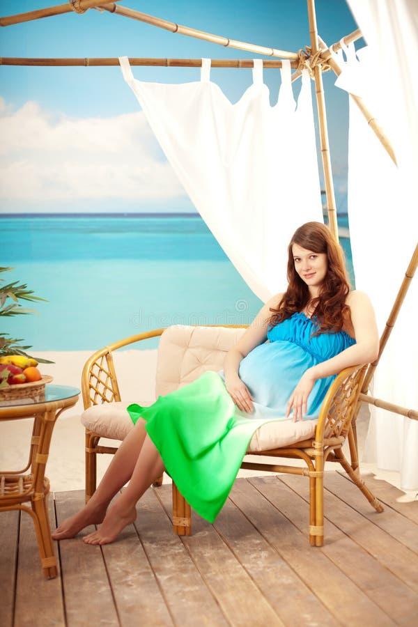 Zwangere vrouw op het strand in bungalow royalty-vrije stock afbeeldingen