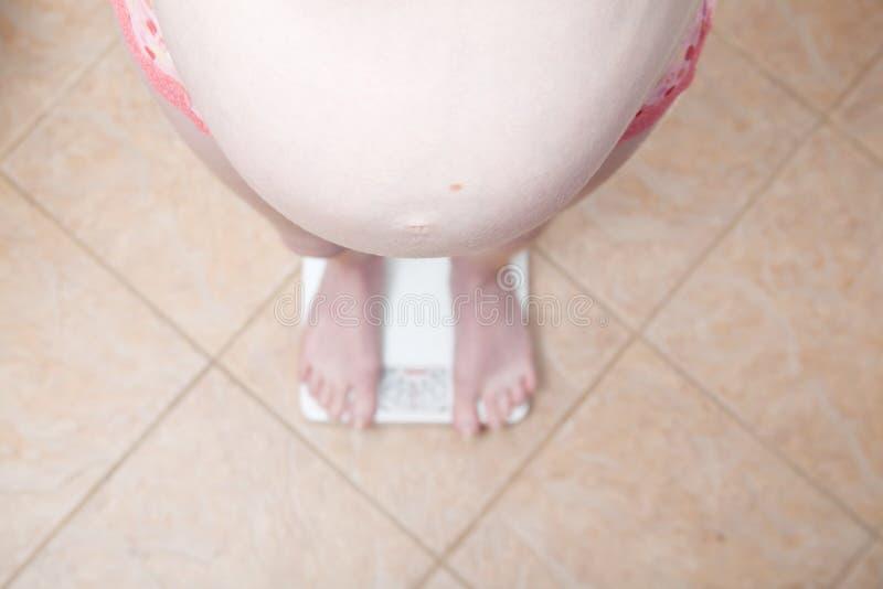 Zwangere vrouw op schalen stock foto's