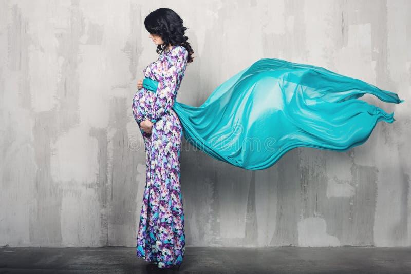 Zwangere vrouw over grijze achtergrond royalty-vrije stock fotografie