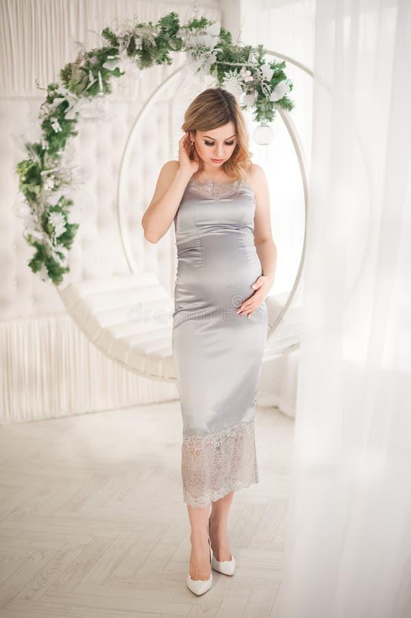 Zwangere vrouw in peignoir met schommeling dat voor het Nieuwjaarclose-up verfraaid is Een vrouw die op een baby in een zilveren  royalty-vrije stock foto's