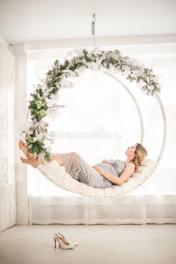 Zwangere vrouw in peignoir met schommeling dat voor het Nieuwjaarclose-up verfraaid is Een vrouw die op een baby in een zilveren  royalty-vrije stock fotografie