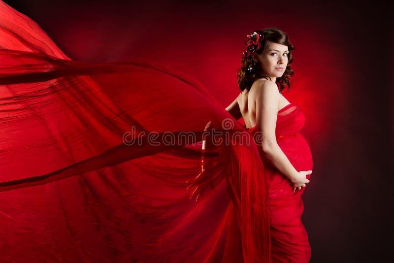 Zwangere vrouw in rode golvende kleding stock fotografie