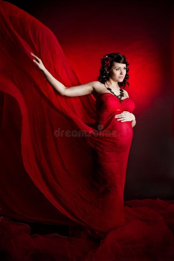 Zwangere vrouw in rode golvende vliegende kleding. royalty-vrije stock afbeelding