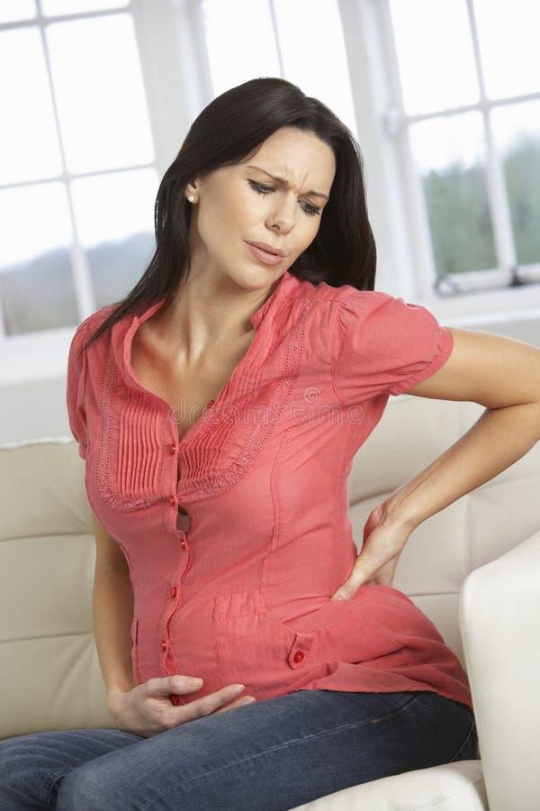 Zwangere Vrouw thuis met Rugpijn stock afbeeldingen