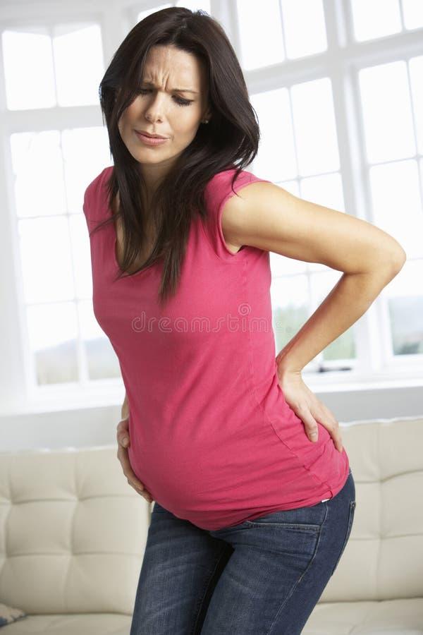 Zwangere Vrouw thuis met Rugpijn royalty-vrije stock foto's
