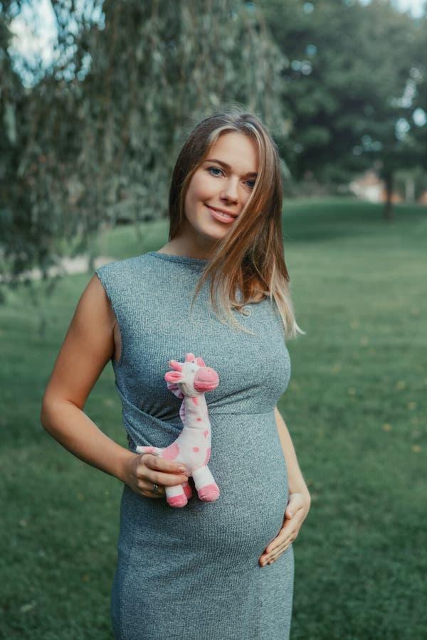 Zwangere vrouw wat betreft haar buik en holdingsroze gevulde pluchestuk speelgoed giraf royalty-vrije stock fotografie