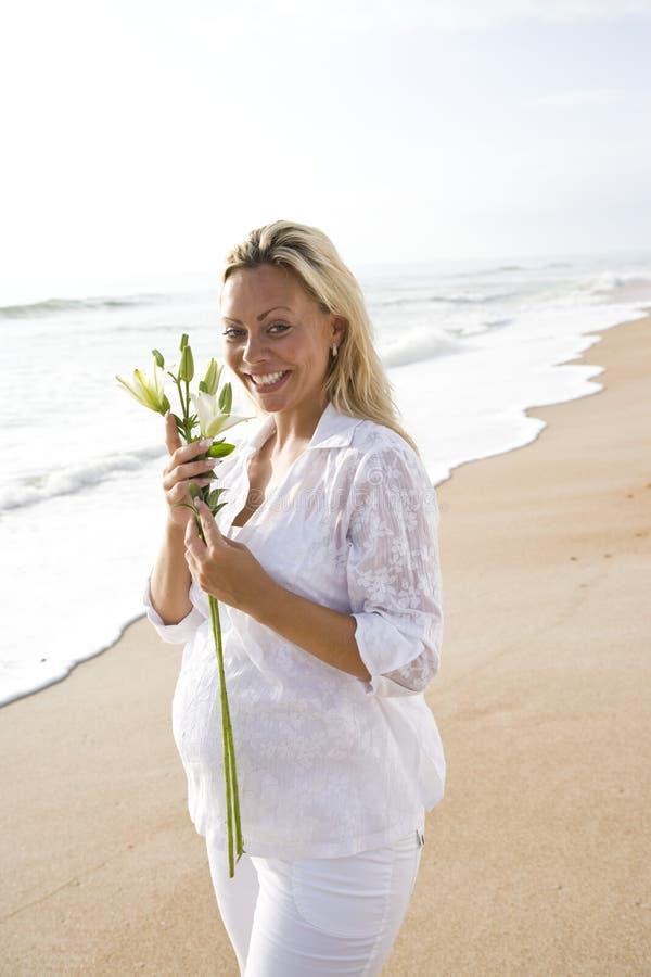 Zwangere vrouw in wit op de bloem van de strandholding royalty-vrije stock afbeelding