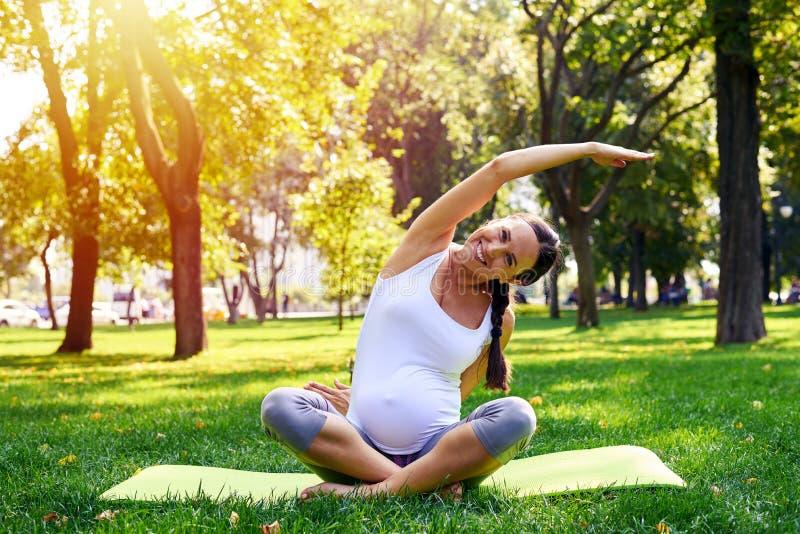 Zwangere vrouw in zich het goede vorm uitrekken op yogamat in openlucht stock foto's