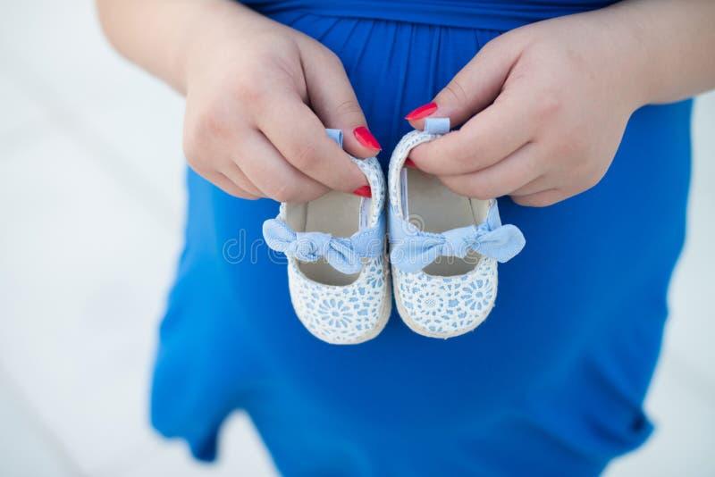 Zwangere vrouw, Zwangerschap, Vader en moeder, die nieuw babymeisje, nieuwe - geboren baby, Schoenen van nieuw wachten - geboren  royalty-vrije stock fotografie