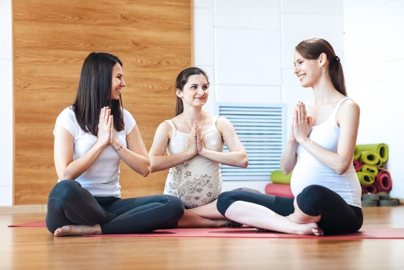 Zwangere vrouwen in de zitting die van de yogaklasse op matten wapens in een geschiktheidsstudio uitrekken royalty-vrije stock fotografie