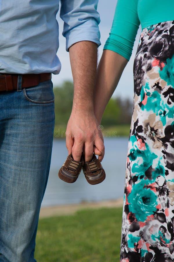 Zwangere vrouwen die babyschoenen houden stock afbeeldingen