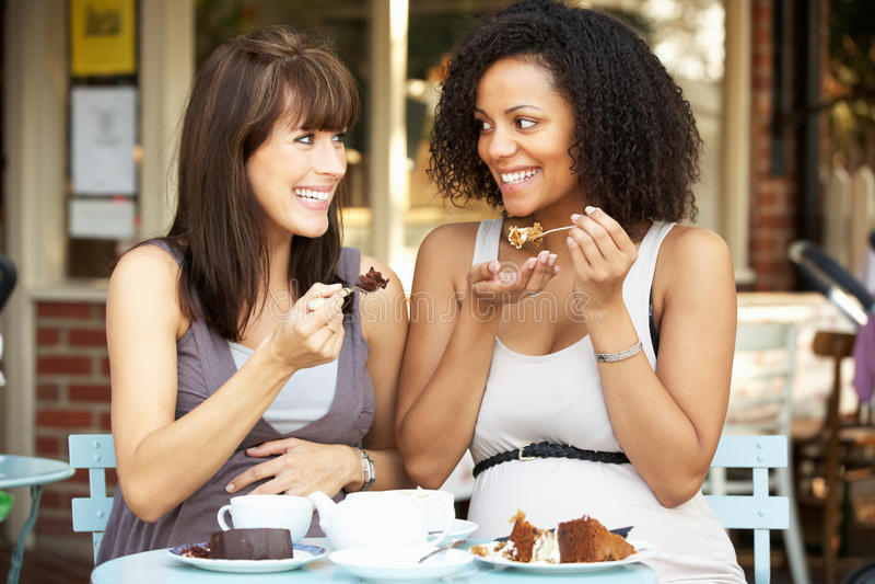 Zwangere vrouwen die buiten koffie zitten royalty-vrije stock afbeelding