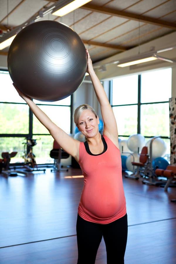 Zwangere vrouwen die uitrekkende oefening doen. stock foto's
