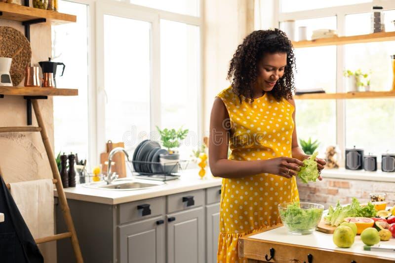 Zwangere vrouwen hakkende sla om wat salade te maken stock afbeeldingen