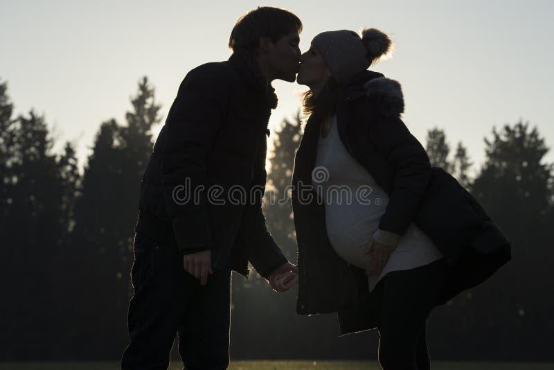 Zwangere vrouwen kussende partner in openlucht royalty-vrije stock fotografie