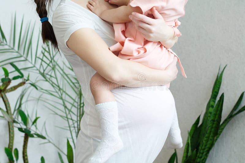 Zwangere vrouwen met dochter, zwangerschapsbuik van vrouw met kind Gelukkig moederschap Het verwachten van babygeboorte in derde  stock fotografie