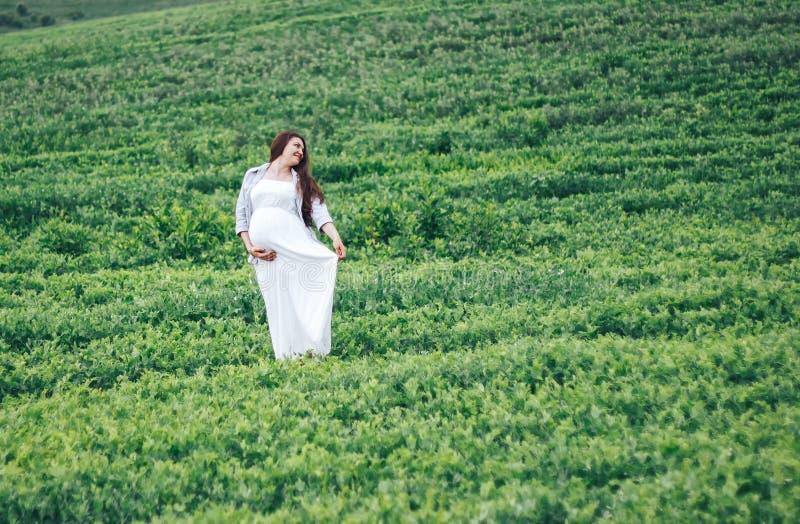 Zwangere vrouwen op groen gebied in witte kleding stock foto