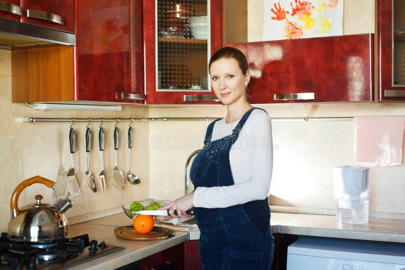 Zwangere vrouwen scherpe sinaasappelen voor haar ontbijt stock foto's