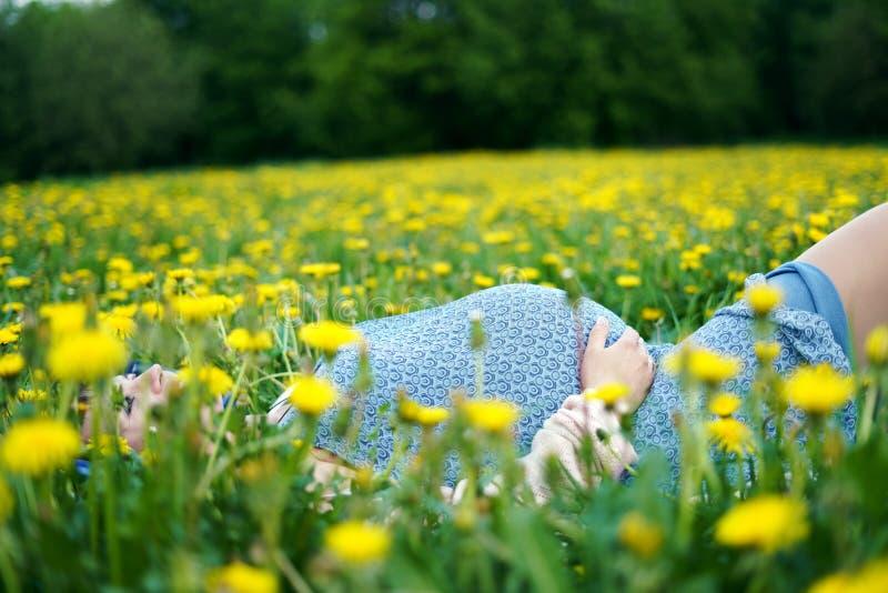 Zwangere vrouwenbuik Zwangere buik dichte omhooggaand Verwachtend wijfje wat betreft buik openlucht in de lentepark, stock foto's