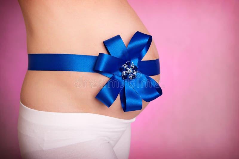 Zwangere vrouwenbuik op roze royalty-vrije stock afbeeldingen