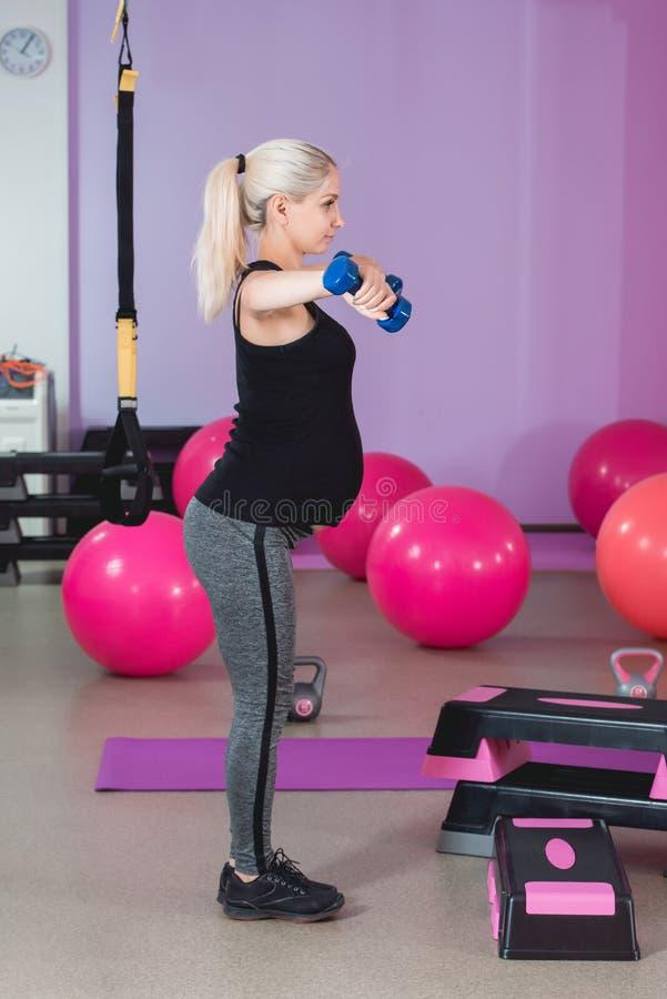 Zwangere vrouwentribune in de gymnastiek die, die haar gewichten op 9 maand met mooi zicht houden en oefening op schouders doen e stock afbeeldingen