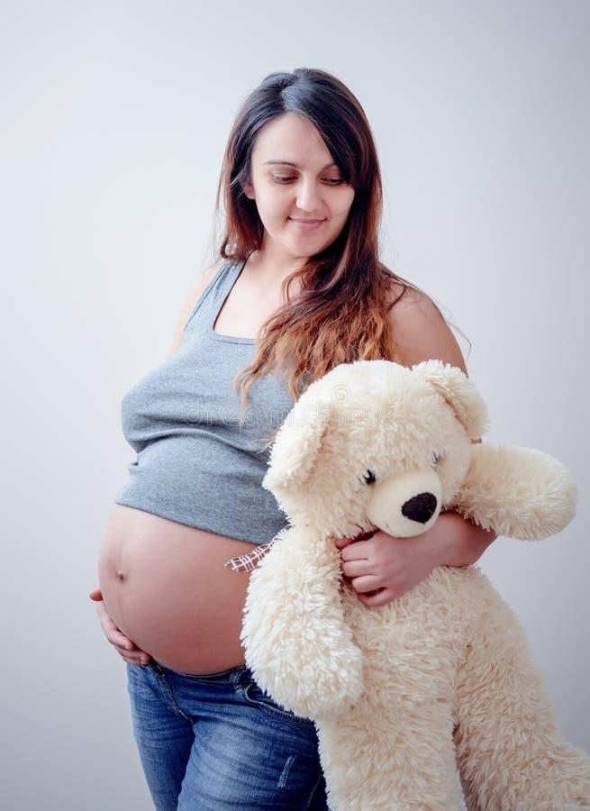 Zwangere vrouwentribunes die een witte teddybeer houden stock foto's