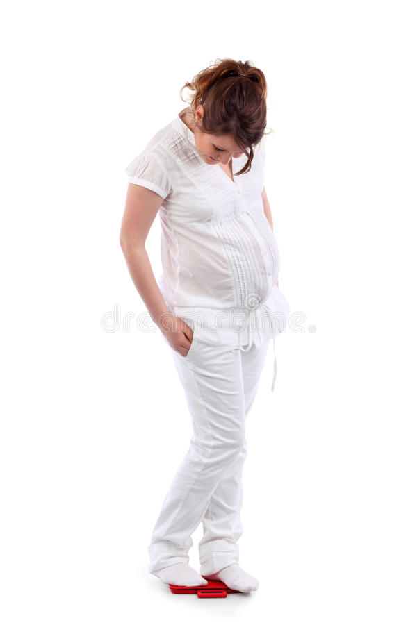 Zwangere vrouwentribunes op rood saldo royalty-vrije stock afbeelding