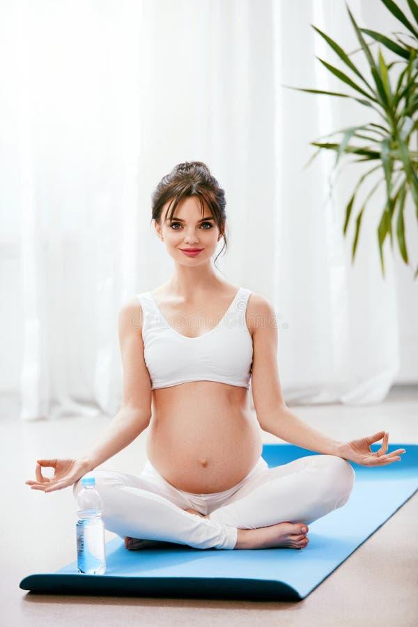 Zwangere vrouwenyoga Zwanger Meisje die thuis uitoefenen stock fotografie